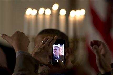 Obama at the earlier holiday reception, obscured by raised smart fone cameras