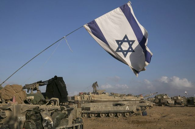 Israeli tanks and armoured personnel carriers are seen at a staging area outside the central Gaza Strip